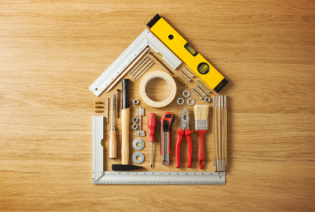 An assortment of handyman and carpentry tools arranged in the shape of a house