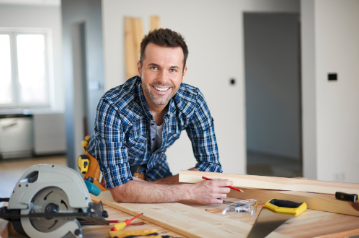 Handsome smiling carpenter taking measurements