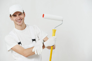 Young capable handyman holding roller paint brush