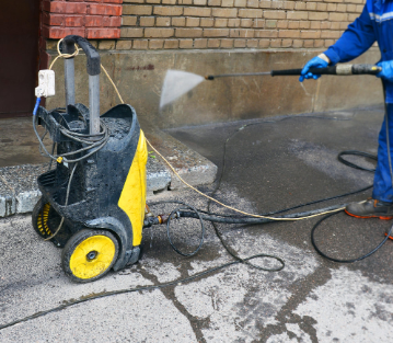 Handyman power washing exterior of brick buildingPicture