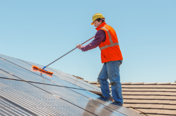 Handyman wearing safety equipment cleaning solar panels on a roof