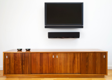OLED TV Mounted on a white wall above wooden cabinet