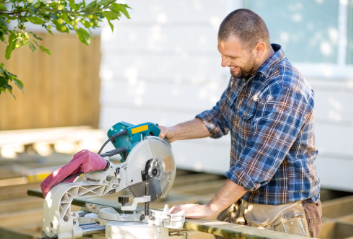 Smiling carpenter using chop saw to cut board to build patio outdoors