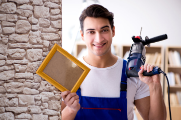 Smiling young handyman about to hang a picture on the wall