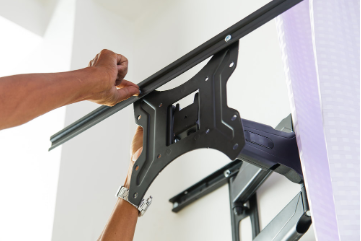 Worker installing TV swivel mount bracket to wall